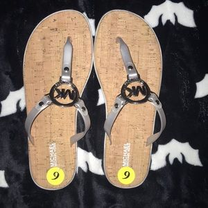 Silver sandals with a bamboo looking foot pad.